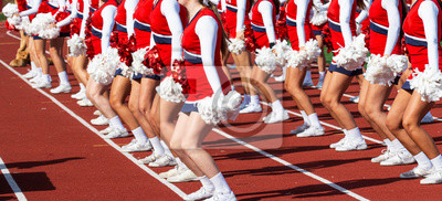 Obraz High school cheerleaders perfomring on a track during football game