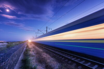 High speed passenger train in motion on the railroad at summer night. Moving blurred modern commuter train at dusk. Railway station and purple sky with moon and clouds. Industrial landscape. Transport