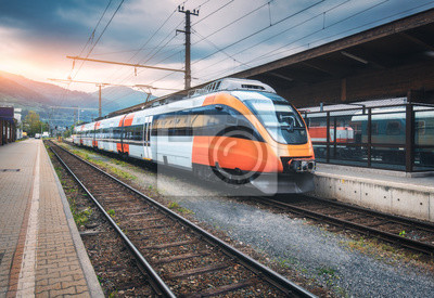 High speed train on the railway station in mountains at sunset in summer. Orange modern commuter train on the railway platform. Industrial landscape with railroad. Passenger transportation. Intercity