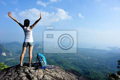 Obraz hiker pewność kobieta silne ramiona otwarte na szczyt górski w skale