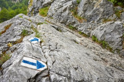 Hiking trail blue paint arrow marking on a rock, selective focus.