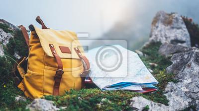 Obraz Hipster wycieczkowicz turystyczny żółty plecak i mapa Europy na tle zielonej trawy natura w górach, niewyraźne panoramiczny krajobraz, podróżnik zrelaksować wakacje koncepcja, widok planowania drogi w