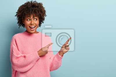 Obraz Horizontal shot of positive lovely woman with Afro haircut, points away with both fore fingers, demonstrates copy space for your information, has appealing look, sincere smile on face. Advertisement