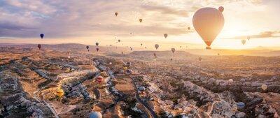 Obraz Hot air balloons flying above Göreme, Cappadocia (Kapadokya) Anatolia, Turkey at sunrise. Panoramic view of villages and fairy chimneys. Popular touristic destination for summer vacation holidays