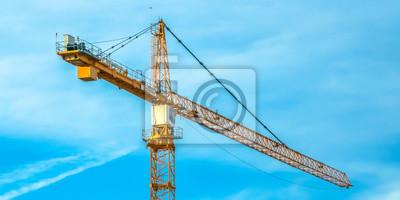 Obraz Huge construction tower crane and cloudy blue sky