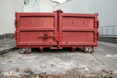 Obraz huge red metal garbage container between light walls of large buildings on backstreet