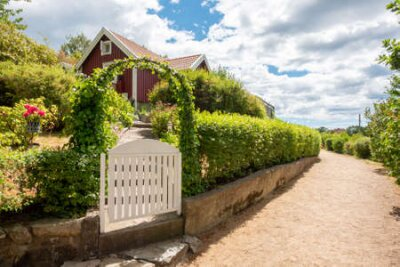Obraz image of Narrow gravel lane beside red and white traditional allotment cabin with picket fence and flowers. Location Karlskrona in Sweden.