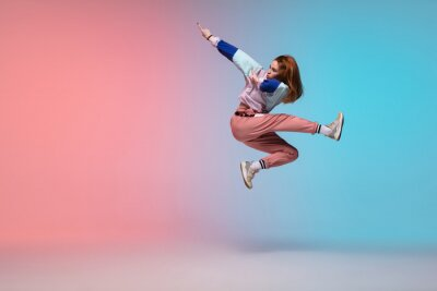 Obraz In jump. Beautiful girl dancing hip-hop in stylish clothes on colorful gradient background at dance hall in neon light. Youth culture, movement, style and fashion, action. Fashionable bright portrait.