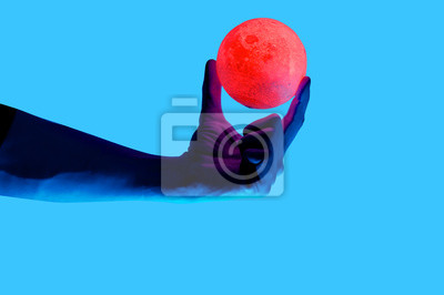 Obraz Isolated on blue background photo of man holding moon shape illuminated sphere. Surrealistic collage style, contemporary art element for design, posters and banners. Neon purple light. Pop inspiration