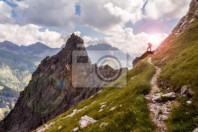 Obraz Jeden turysta na wąskiej górskiej ścieżce w świetle słonecznym