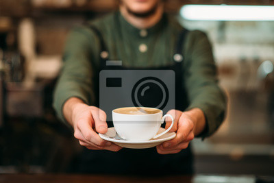 Obraz Kelner w czarnym fartuchu rozciąga kawę