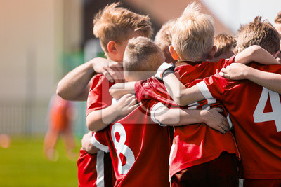 Obraz Kids Play Sports Game. Children Sporty Team United Ready to Play Game. Children Team Sport. Youth Sports For Children. Boys in Sports Jersey Red Shirts. Young Boys in Soccer Sportswear