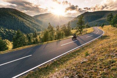 Obraz Kierowca motocykla jedzie po alpejskiej drodze