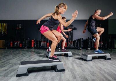 Obraz Klasy trener kobieta robi aerobik z steppery w siłowni