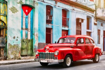 Obraz Klasyczny samochód i stary budynek z kubańską flagą w Old Havana