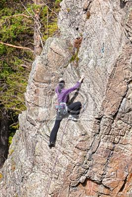 Kobieta alpinistą na stromym klifie.