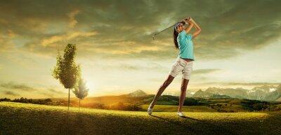 Obraz Kobieta golfa uderzając piłkę w pięknej scenerii