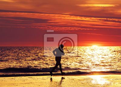 Kobieta jogger działa na plaży o zachodzie słońca.