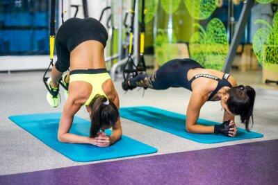 Obraz Kobieta korzystania z ramiączkami zawieszenia w klubie fitness lub siłowni.