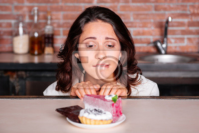 Obraz Kobieta na diecie głodu zjeść ciastko