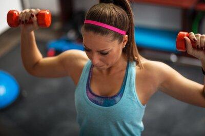 Obraz Kobieta podnoszenia ciężarów i pracy na ramionach na siłowni