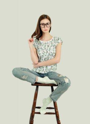 kobieta siedzi na drewniany stołek barowy, studio strzał, patrząc na kamery