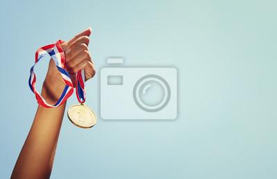 Obraz Kobieta strony podniósł, trzymając złoty medal z nieba. Nagroda i zwycięstwo koncepcji