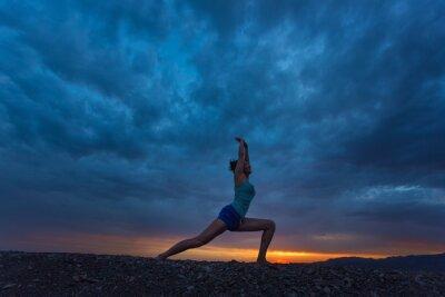 Obraz Kobieta uprawiania jogi stanowi wojownik zewnątrz nad zachodem słońca niebo z powrotem