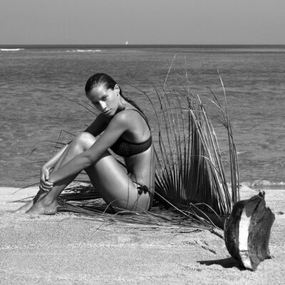 Obraz Kobieta w bikini z gałęzi palmy na plaży w pobliżu morza korzystających słońce. Długie mokre włosy. Tom kręcone fryzura. Kraje tropikalne. Gorący letni dzień. Sexy dziewczyna. Wakacje. Zdjęcie z wyspy