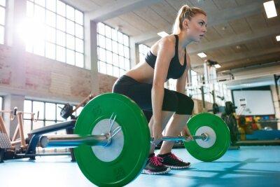 Obraz Kobieta w siłowni robi ciężkich ćwiczeń waga