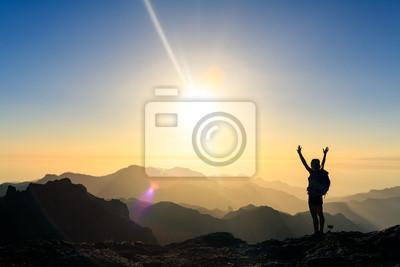 Obraz Kobieta wycieczkuje sukces sylwetkę w góra zmierzchu
