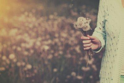 Obraz Kobieta z bukietem kwiatów mniszka lekarskiego w ręku