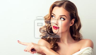 Obraz Kobiety niespodzianka pokazuje produkt Piękna dziewczyna z kędzierzawym włosy wskazuje strona. Prezentujesz swój produkt. Pojedynczo na białym tle. Wyraziste mimikę twarzy