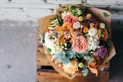 Obraz Kolorowe bukiet ró? Nych? Wie? Ych kwiatów przeciwko mur ceglany. Bukiet storczyków, róży, frezji i liści eukaliptusa. Rustykalne tło kwiatu