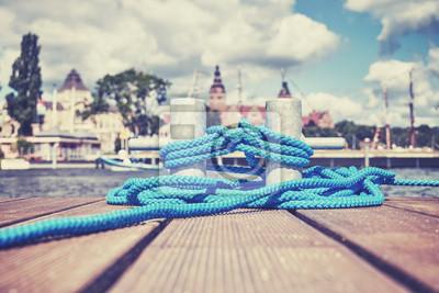 Kolorowy stonowany obraz kluczyka z niebieską liną na drewnianym molo, Szczecin nabrzeża w oddali, Polska.