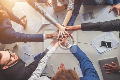Obraz Koncepcja jedności. Close-up osób posiadających ręce razem, siedząc wokół biurka
