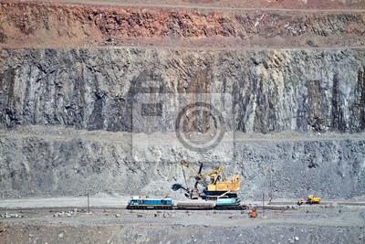 Koparka załaduje rudę żelaza do wagonu towarowego na kopalni odkrywkowej rudy żelaza. Krivoy Rog, Ukraina