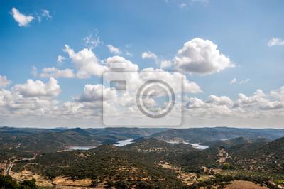 Krajobraz objętych górach z zielonych drzew i błękitne niebo z białymi chmurami, na terenie rezerwatu przyrody piły Aracenie, Huelva, Hiszpania. Między górami jest jezioro