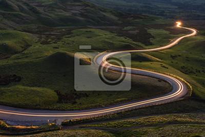 Obraz Krętą krzywą drogę wiejską z lekkim szlakiem prowadzącym przez brytyjskie krajobrazy.