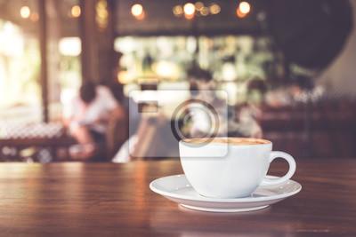 Obraz Kubek gorącej kawy na stole w kawiarni z ludźmi. rocznika i retro efekt kolorystyczny - płytkiej głębi ostrości