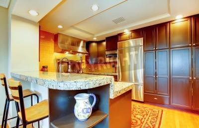 Kuchnia z czarnymi drewnianymi szafkami, marmurowymi blatami, stalowymi aplikacjami i drewnianymi stołkami barowymi