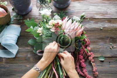 Obraz Kwiaciarnia w pracy: dość młoda blond kobieta mody making nowoczesny bukiet z różnych kwiatów