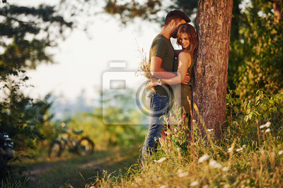 Obraz Leaning on the tree. Beautiful young couple have a good time in the forest at daytime