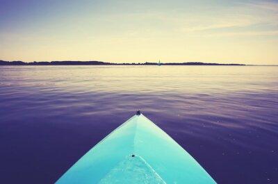 Łęk kajak na spokojnym jeziorze przy zmierzchem, barwi stonowanego obrazek, selekcyjna ostrość.