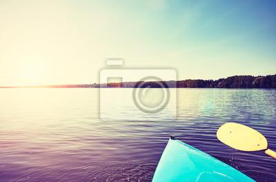 Łęk kajak z paddle na spokojnym jeziorze przy zmierzchem, barwi stonowanego obrazek, selekcyjna ostrość.