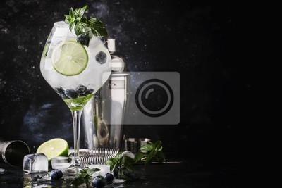Obraz Letni koktajl alkoholowy z jagodami mojito z rumem, zieloną miętą, wapnem i kruszonym lodem, narzędzia barowe, licznik szarego baru, selektywne skupienie