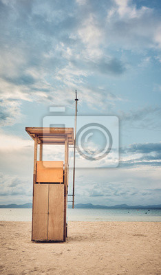 Lifeguard tower on an empty beach at sunset, color toned picture.