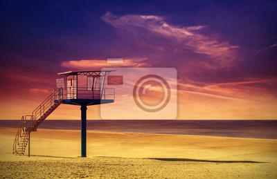 Lifeguard wieża na plaży o zachodzie słońca.