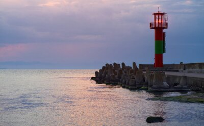Lighthouse protected by concrete breakwater tetrapods at sunset, Swinoujscie, Poland.