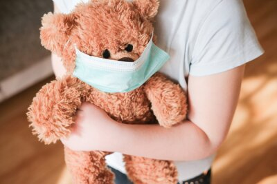 Obraz little girl holding teddy bear in medical mask to protect from coronavirus.